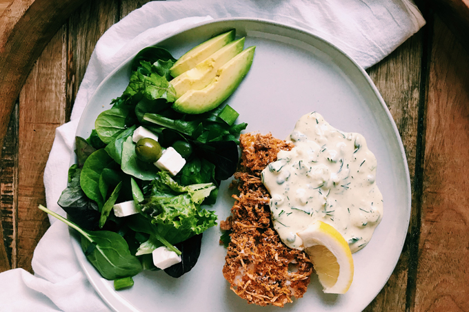Crispy Oven Fried Fish, tartar sauce, lemon, avocado, salad on a white plate with a white towel