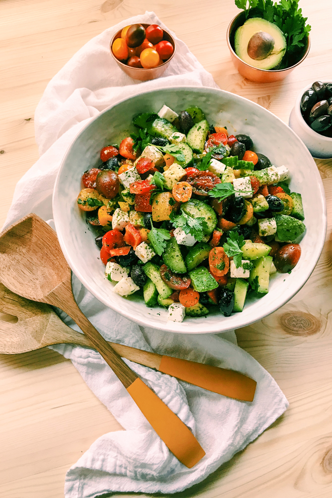a white serving dish with colorful greek salad with feta and olives and peppers and tomatoes and avocado with two wooden spoons resting nearby