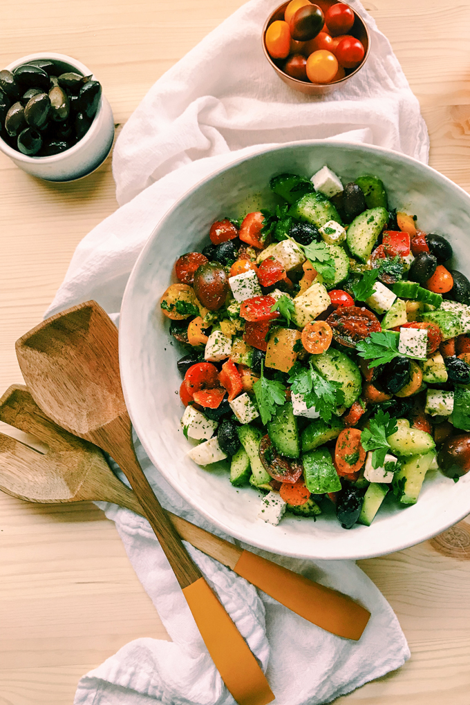 a white bowl with crunchy greek salad two wooden spoons resting to the side