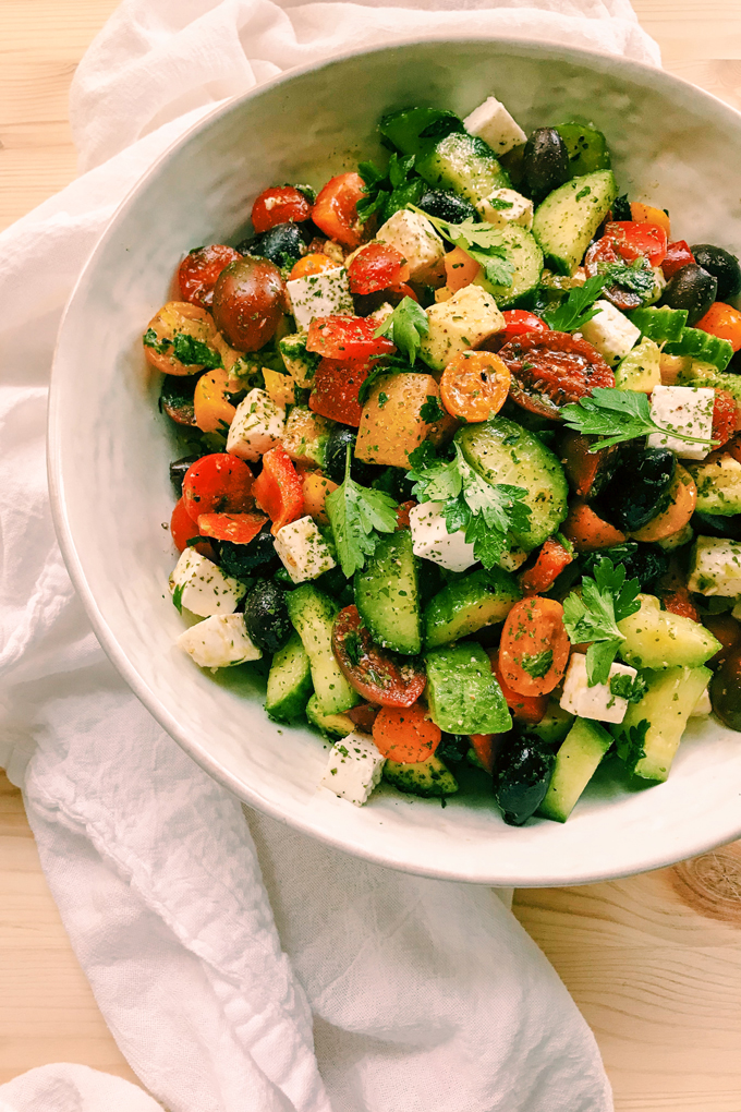 greek salad with peppers, feta, avocado, tomato, olives in a white bowl