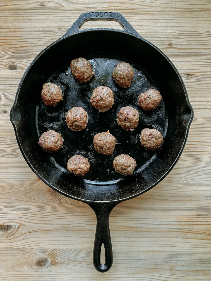 a cast iron pan filled with cooked lamb meatballs resting on a wooden table