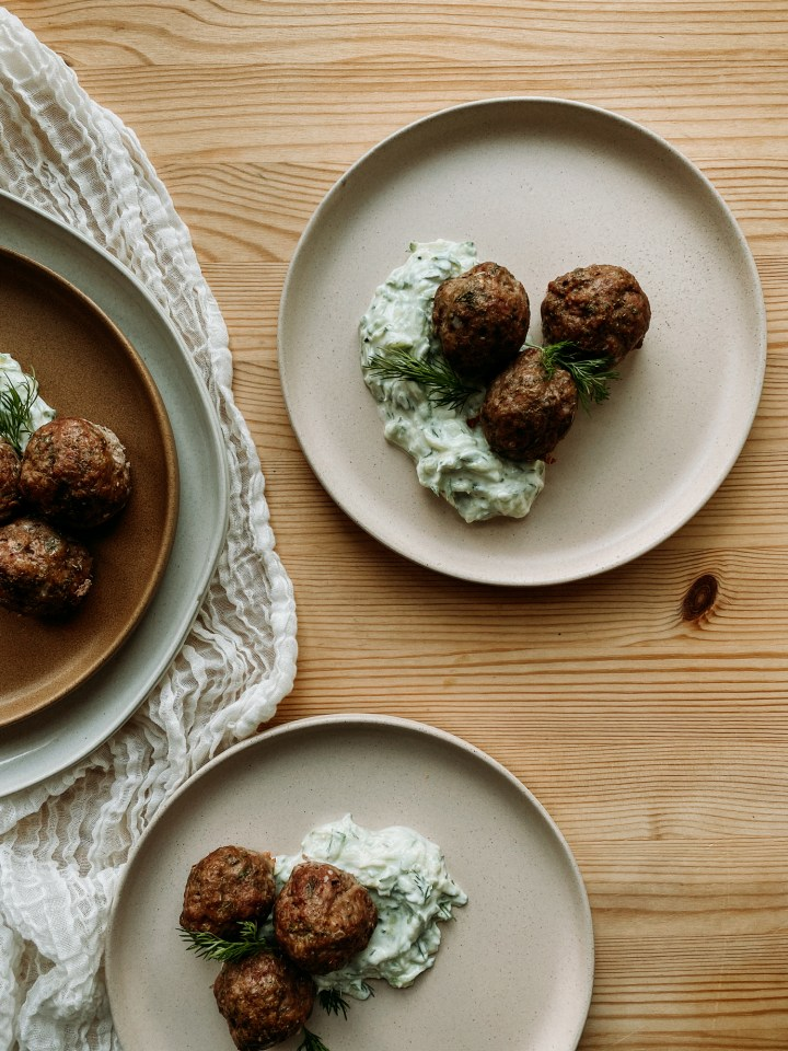 a pink plate containing Greek Lamb Meatballs with Tzatziki Sauce on a wooden surface next to several more plates with meatballs and sauce on a wooden surface