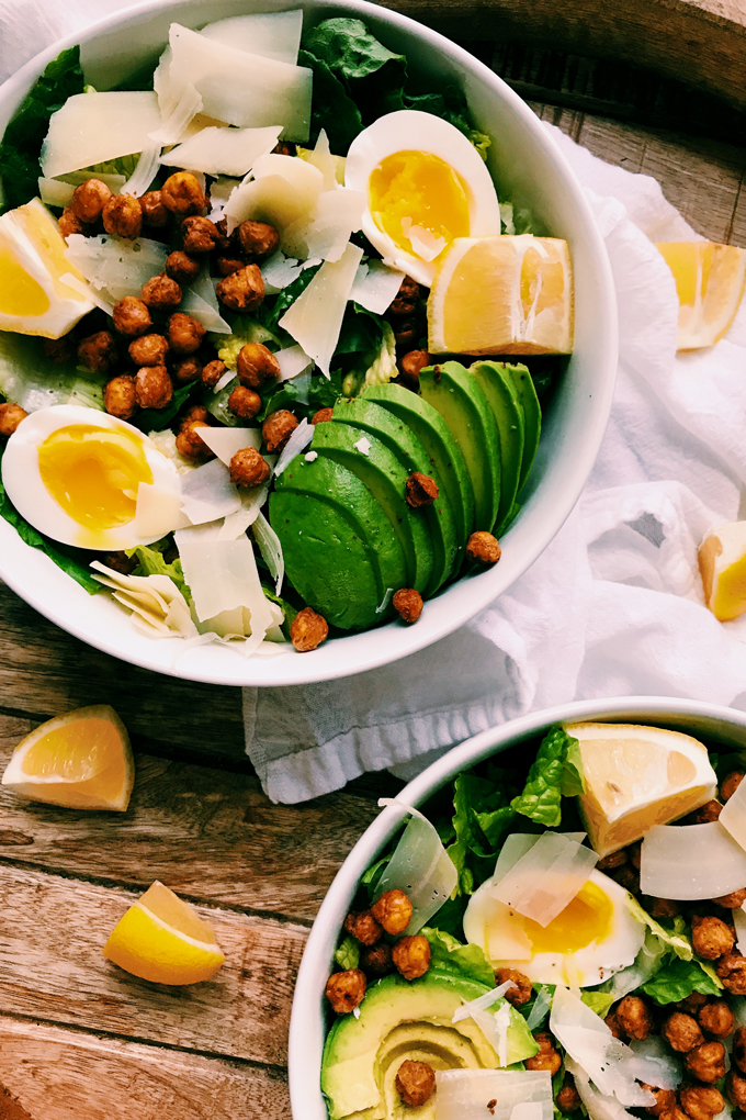white bowls filled with caesar salad on a white towel with lemons