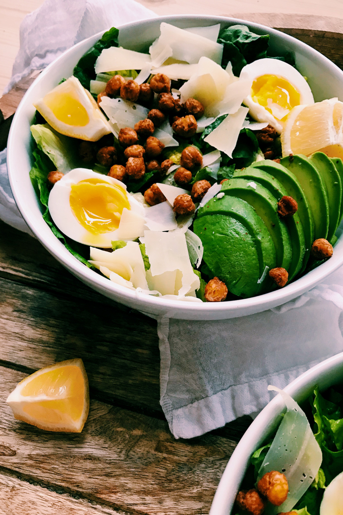 white bowl with avocado, salad, eggs, chickpeas, and lemon