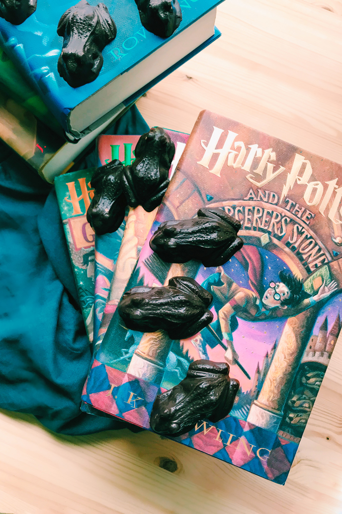 chocolate shaped frogs on a stack of harry potter books and a teal towel