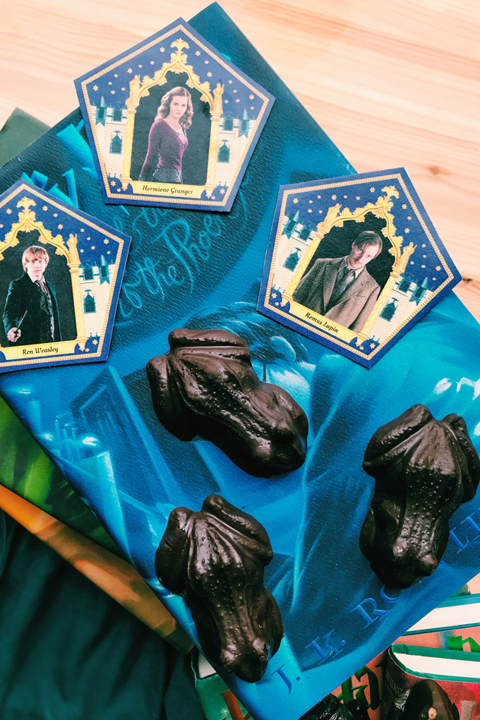 dark chocolates and wizard trading cards resting on a blue book