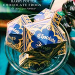 a glass bowl of gold and blue boxes that say chocolate frogs