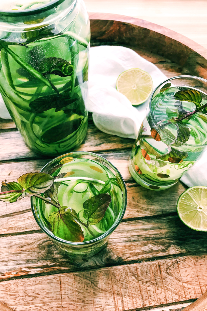 a container of cucumber mint water with lime and two glasses full of it on a wooden tray