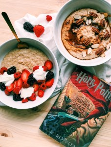 two white bowls with scottish oatmeal, red berries, black berries, yogurt, pecans, almonds, coconut sugar, harry potter book nearby