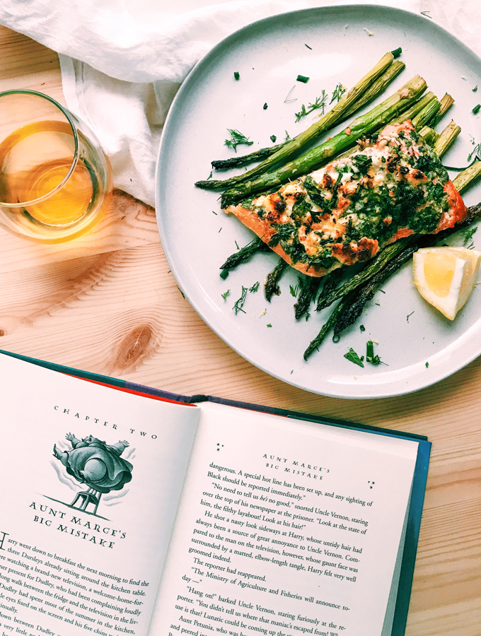 an open book next to a white plate of salmona nd asparagus with a glass of white wine