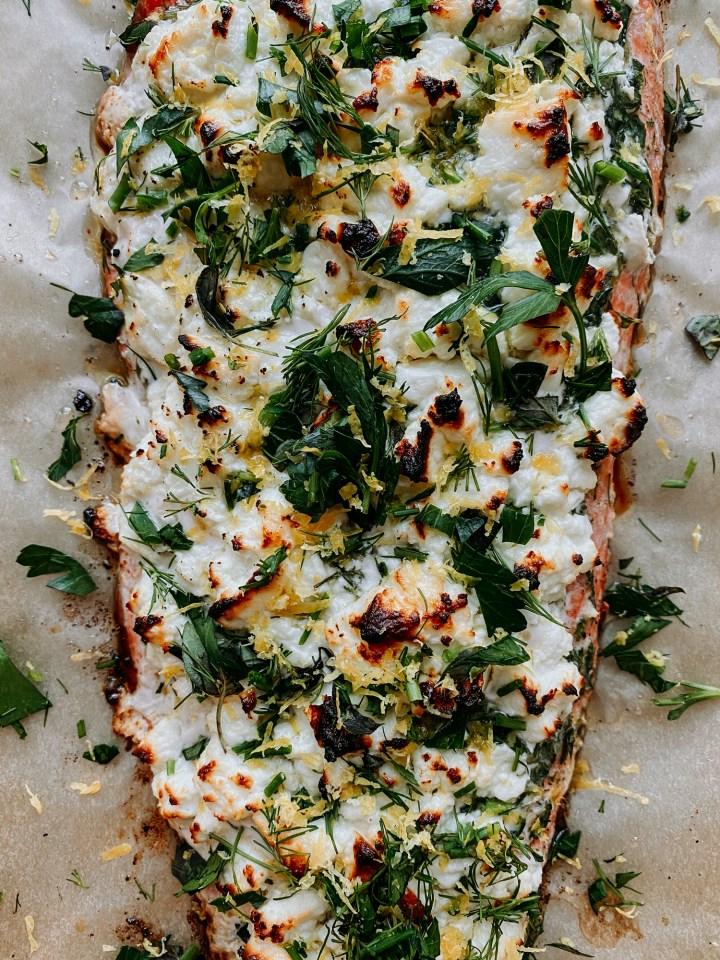a closeup of charred feta cheese and herbs on top of salmon