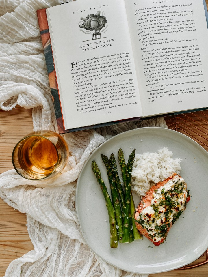 an open harry potter booka nd a glass of white wine next to a plate with petunia dursleys fancy roasted salmon, asparagus, and white rice