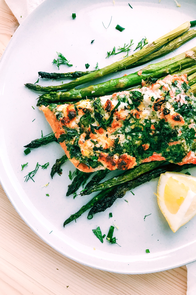 a white plate with salmon and asparagus and lemon and herbs