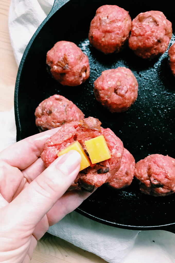 a hand pressing cheese into a raw meatball with more meatballs in a cast iron pan int he background
