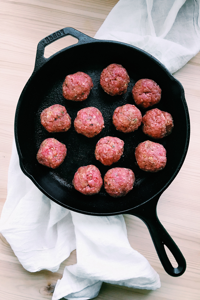 a cast iron pan of raw meatballs on a white towel