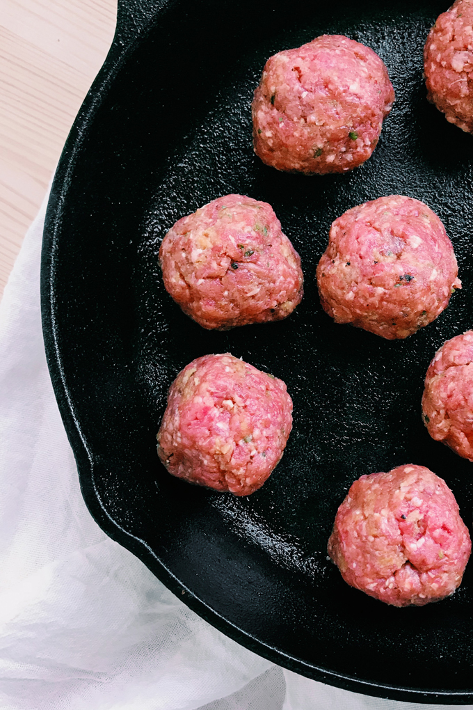 closeup of a cast iron pan with raw meatballs
