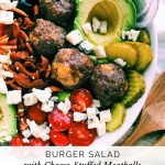 a white salad bowl with burger meatballs, veggies, and salad