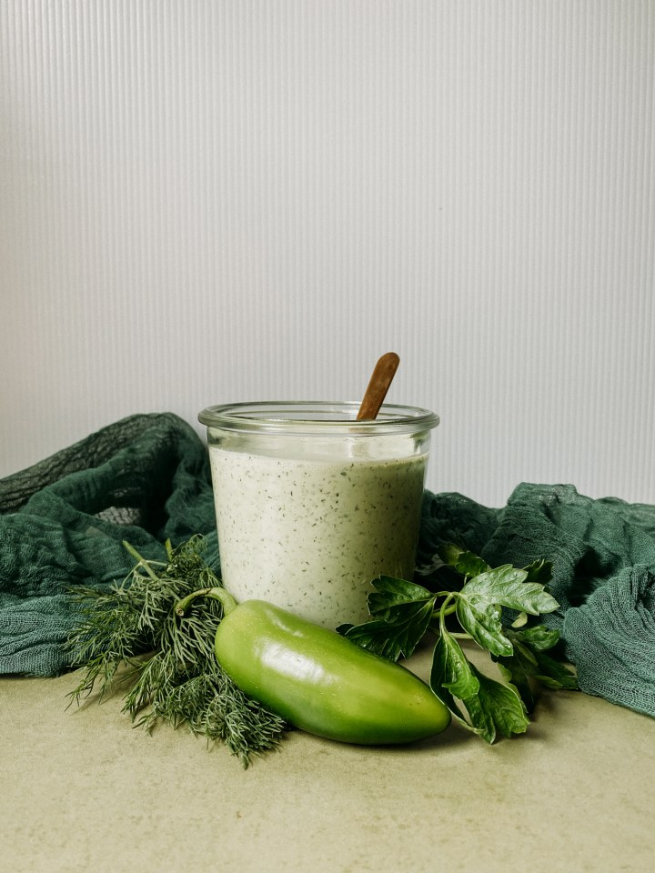a side view of a glass container of Buttermilk Jalapeno Ranch Dressing with jalapenos and herbs surrounding the container