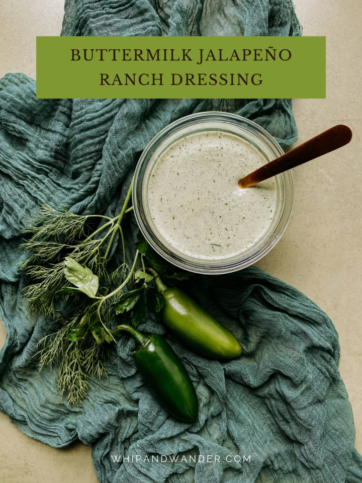 a gold spoon resting in a container of Buttermilk Jalapeno Ranch Dressing on a green cloth