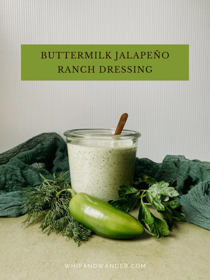 fresh jalapenos and herbs surrounding a glass jar of Buttermilk Jalapeno Ranch Dressing