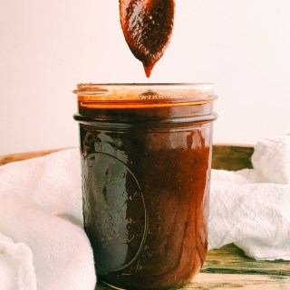spicy red bbq sauce dripping off of a spoon into a jar