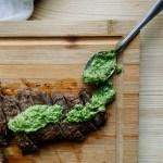 a spoon filled with green sauce next to slices of grilled skirt steak on a wooden cutting board