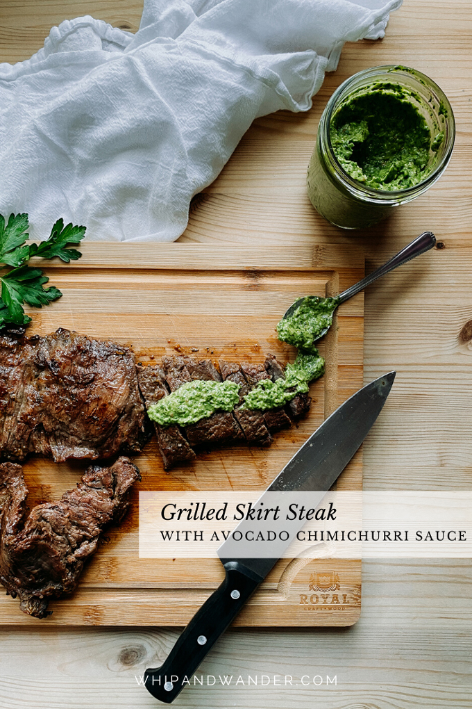a wood cutting board with avocado chimichurri sauce topped grilled skirt steak