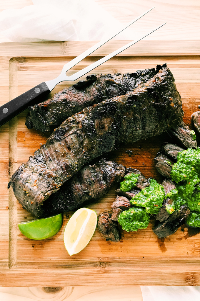 skirt steak on a cutting board with limes and green sauce