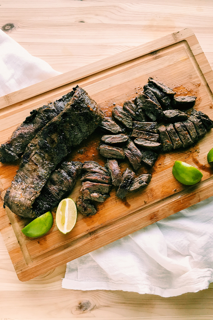 slices of grilled skirt steak and limes