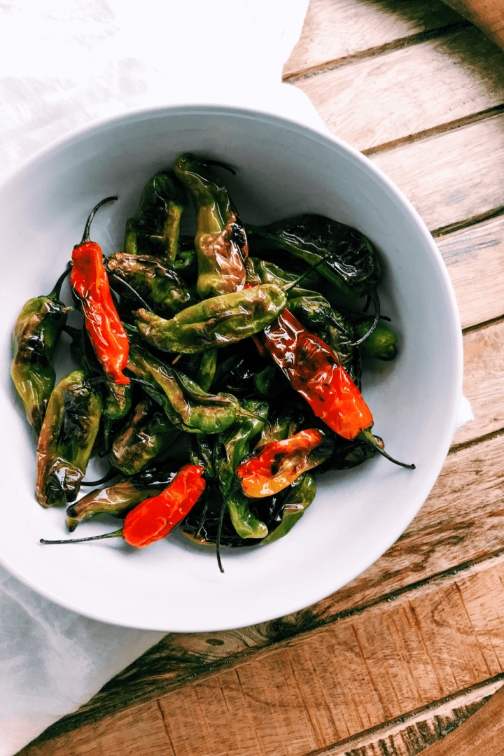 Blistered Shishito Peppers in red and green variety in a white bowl on a wooden surface
