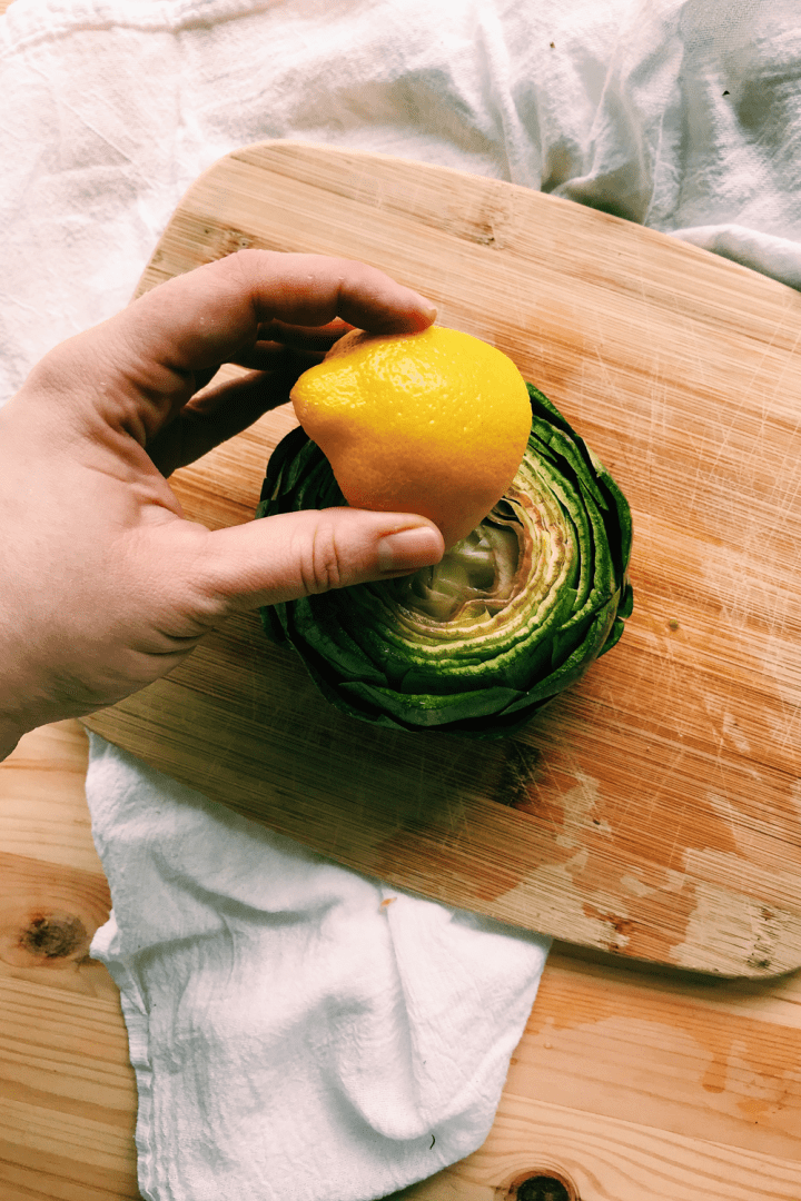 a hand rubbing a raw artichoke with lemon