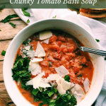 a bowl of Chunky Tomato Basil Soup with a spoon on a white towel draped wooden tray