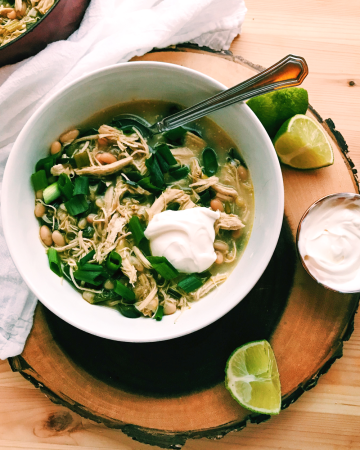 chicken poblanoc hili in a white bowl with a dollop of sour cream on a wooden surface