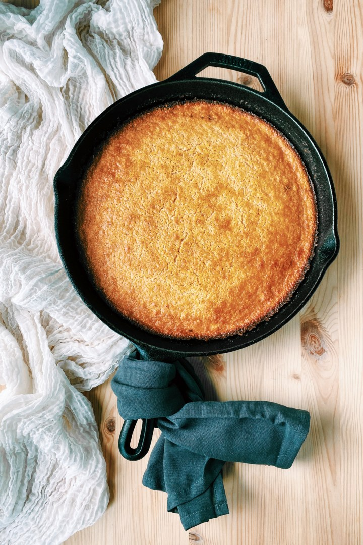 a cast iron skillet of cornbread whos handle is wrapped in a gray towel