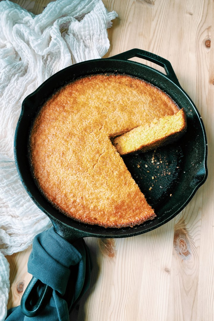 Brown Butter Buttermilk Skillet Cornbread with a wedge of cornbread resting on its side