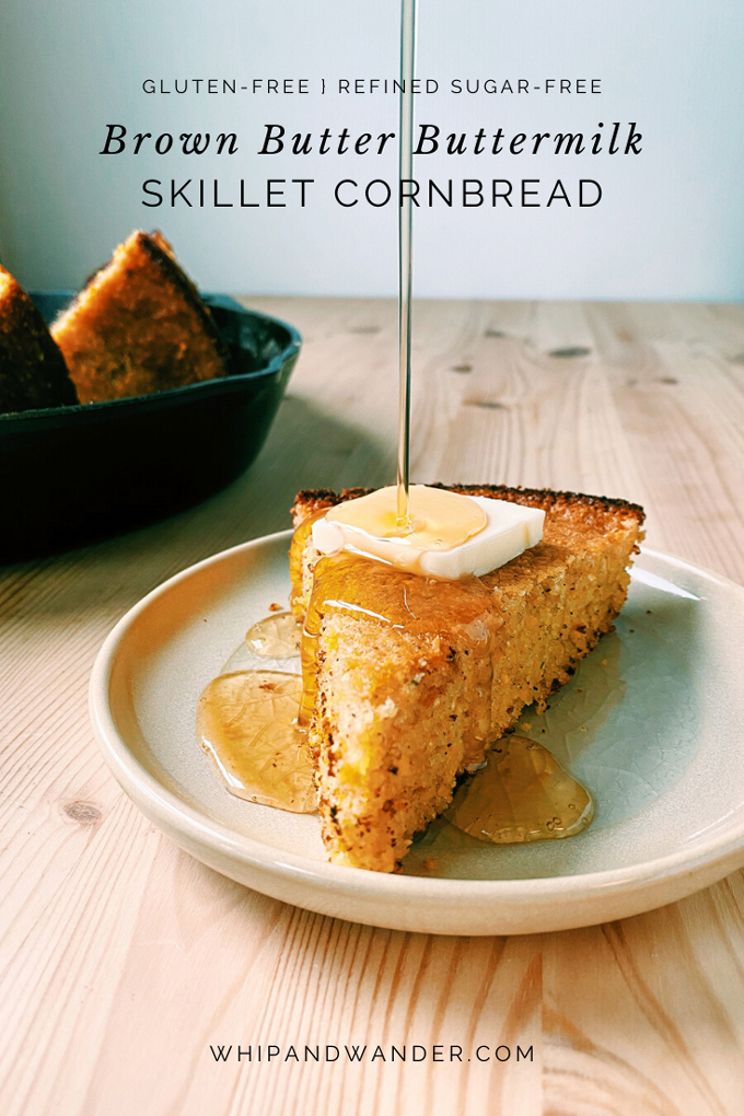a beige plate with a slice of Brown Butter Buttermilk Skillet Cornbread topped with butter and a drizzle of honey dropping onto the top