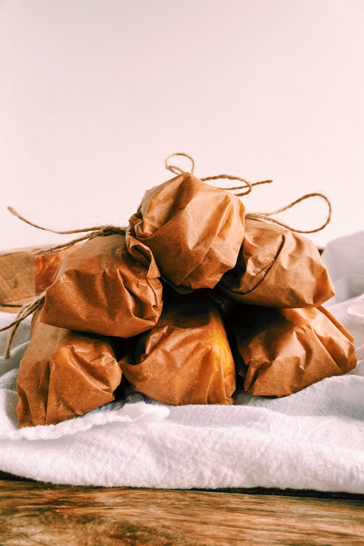 a white towel with 6 tubes of parchment paper wrapped compound butter tied with string