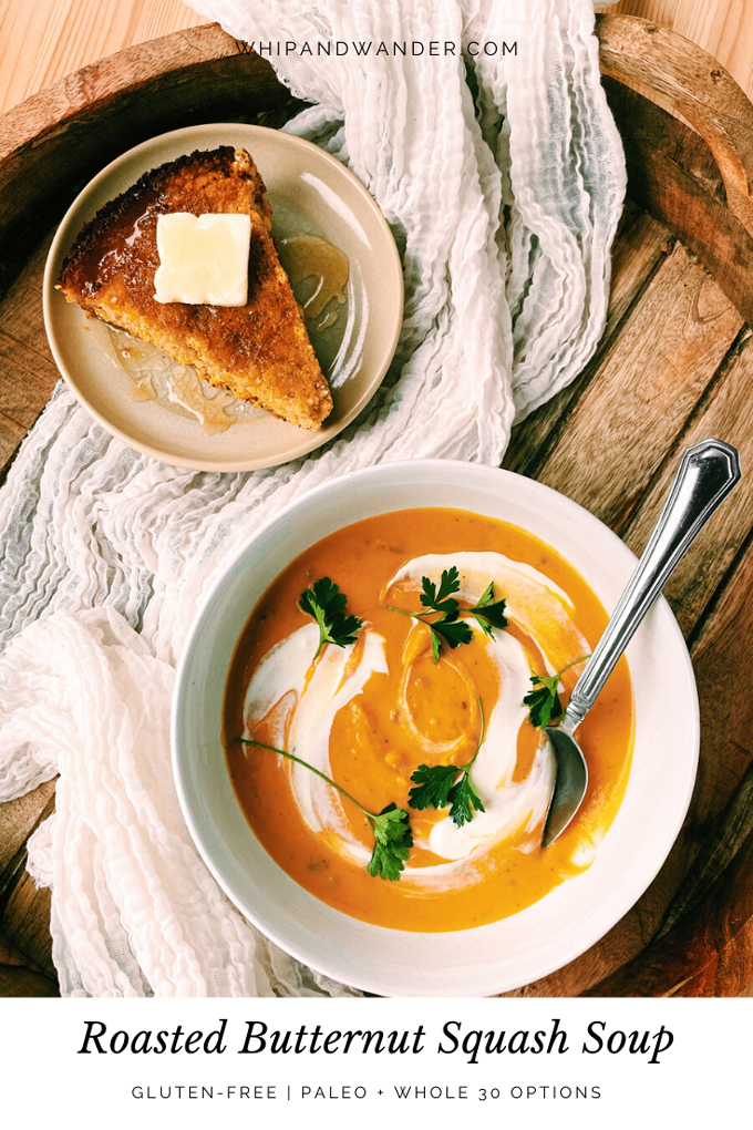 a wooden tray with a bowl of Roasted Butternut Squash Soup and a plate with a slice of cornbread topped with butter and honey