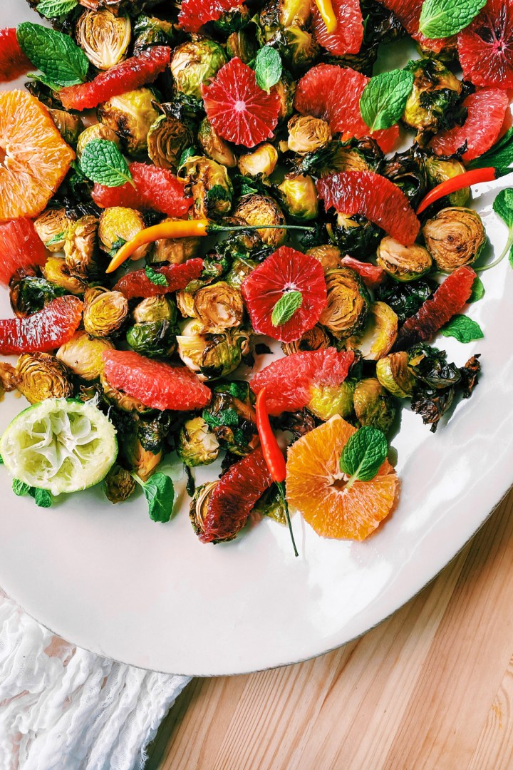 a white platter with Roasted Brussels Sprouts with Fish Sauce and Citrus topped with Thai chili peppers and mint