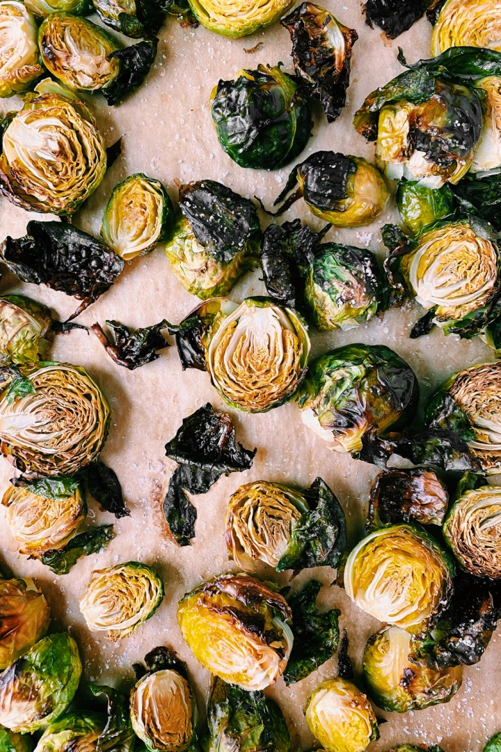 roasted brussels sprout halves on a parchment lined tray