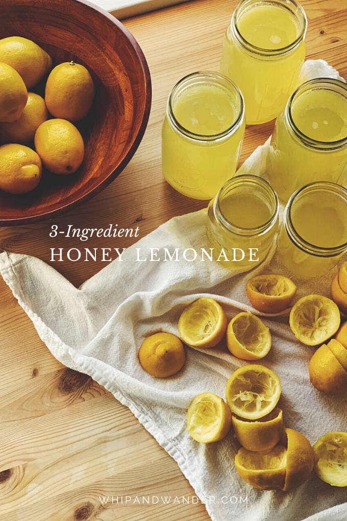 a wooden bowl filled with lemons, mason jars filled with honey lemonade, and squeezed lemon halves on a white towel