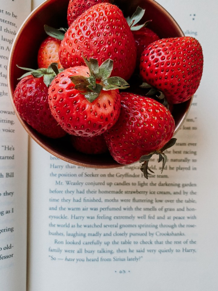 a copper bowl filled with fresh strawberries resting on an open harry potter book
