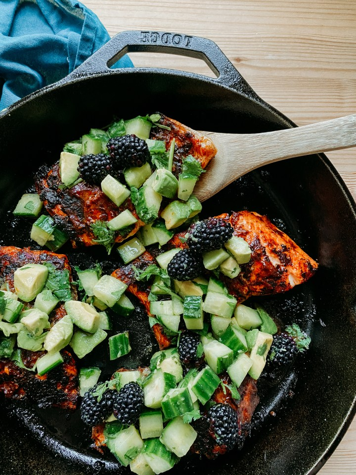 a wooden serving utensil scooping a piece of salmon with adobo sauce and blackberry cucumber avocado salsa out of the cast iron pan