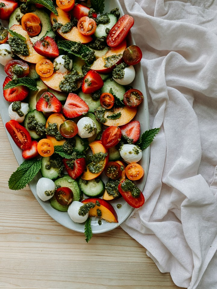 a white serving dish with a peach strawberry summer salad with basil walnut pesto