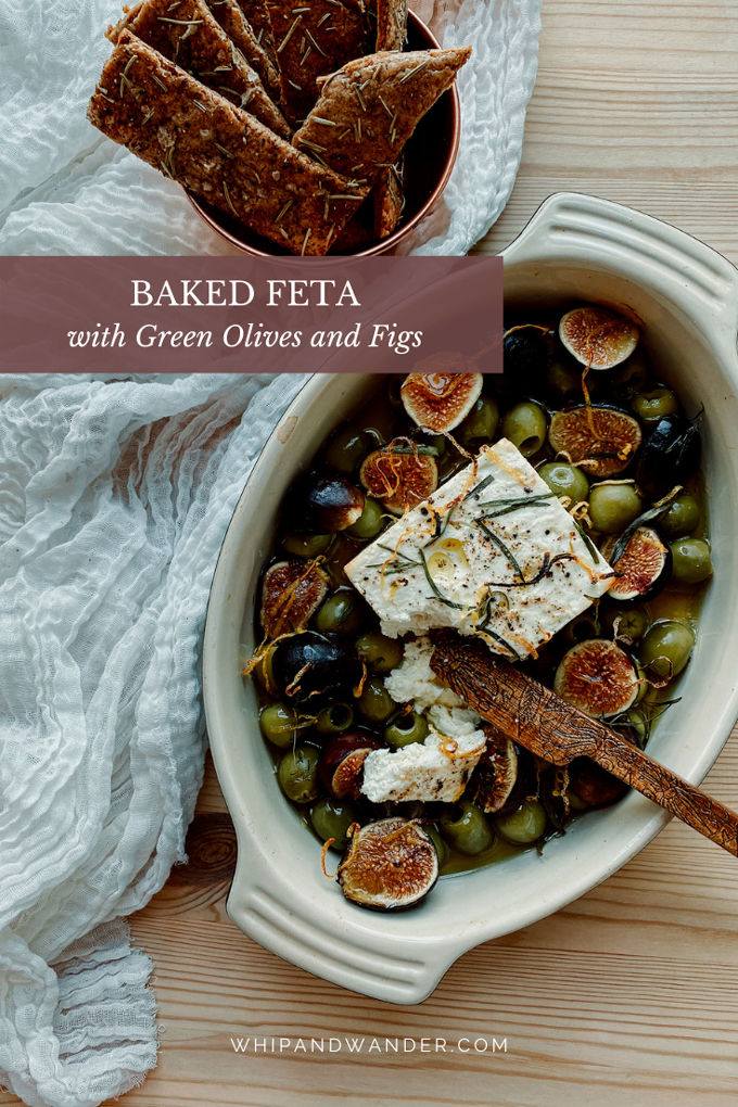 a cheese knife rests in a baking dish of baked feta with olives and figs and herbs