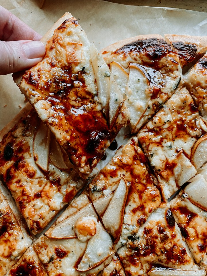 a hand pulling up a slice of Pear and Blue Cheese Pizza