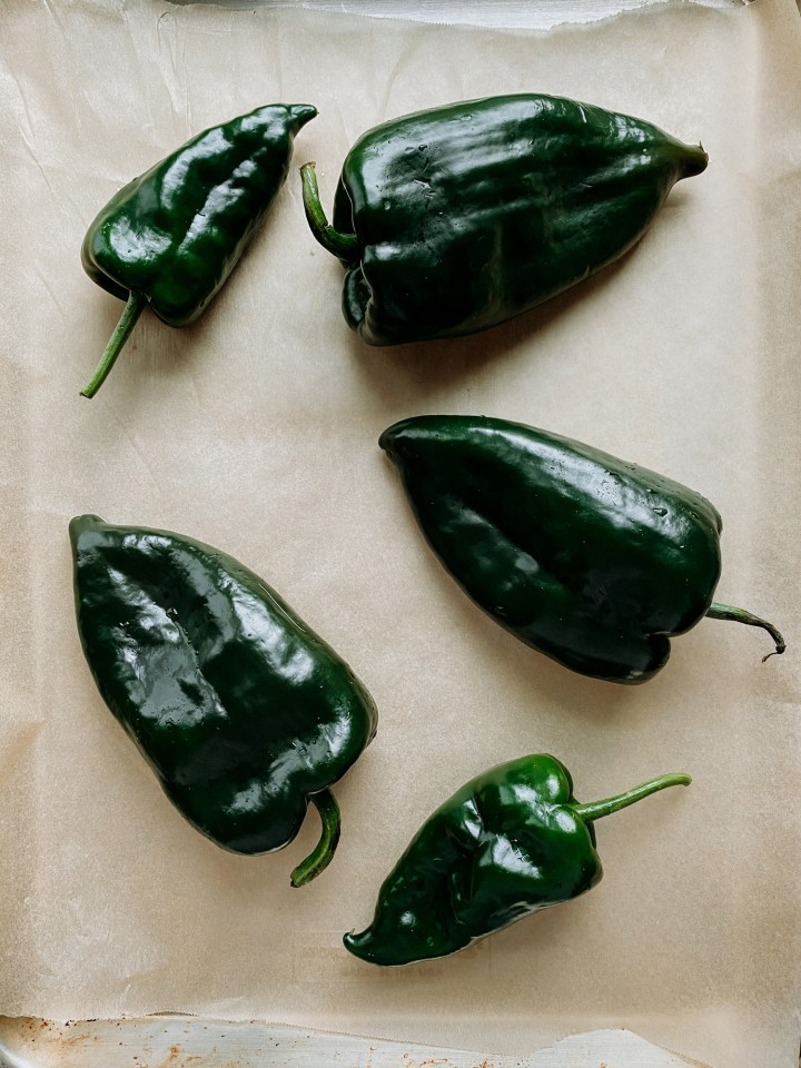 5 fresh poblano peppers resting on a brown parchment line baking sheet