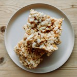 A stack of Salted Brown Butter Crispy Treats on a light pink plate resting on a wooden surface