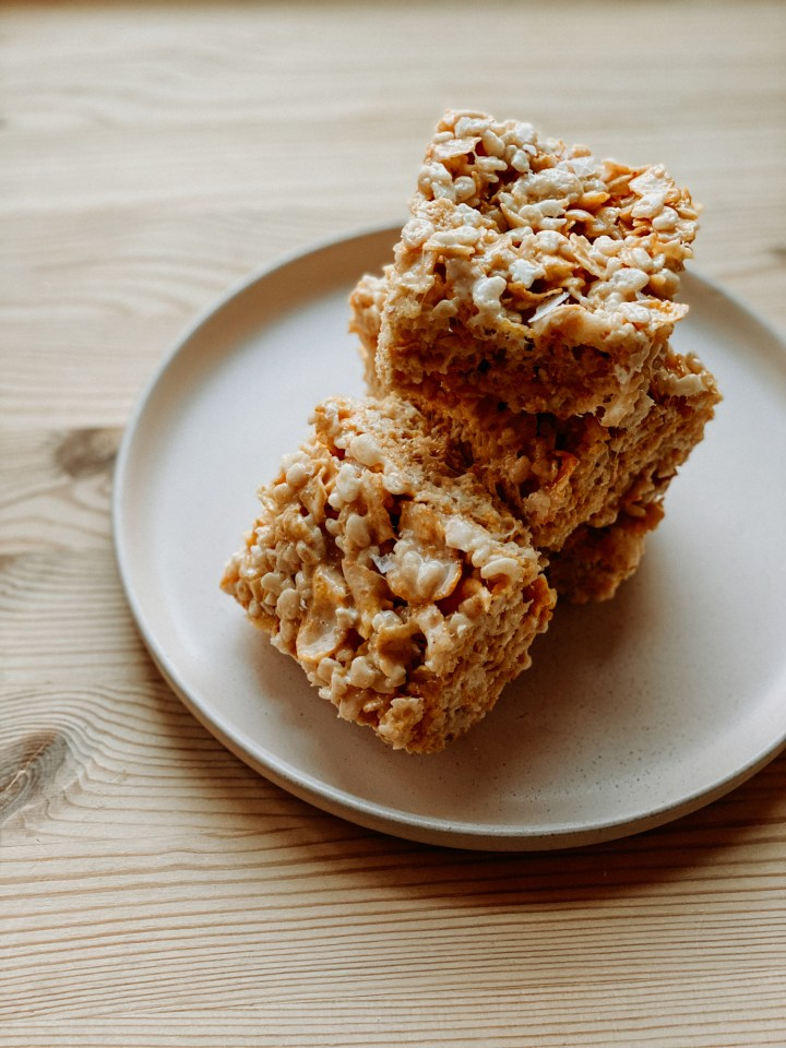 Salted Brown Butter Crispy Treats stacked on apink plate resting on a wooden table