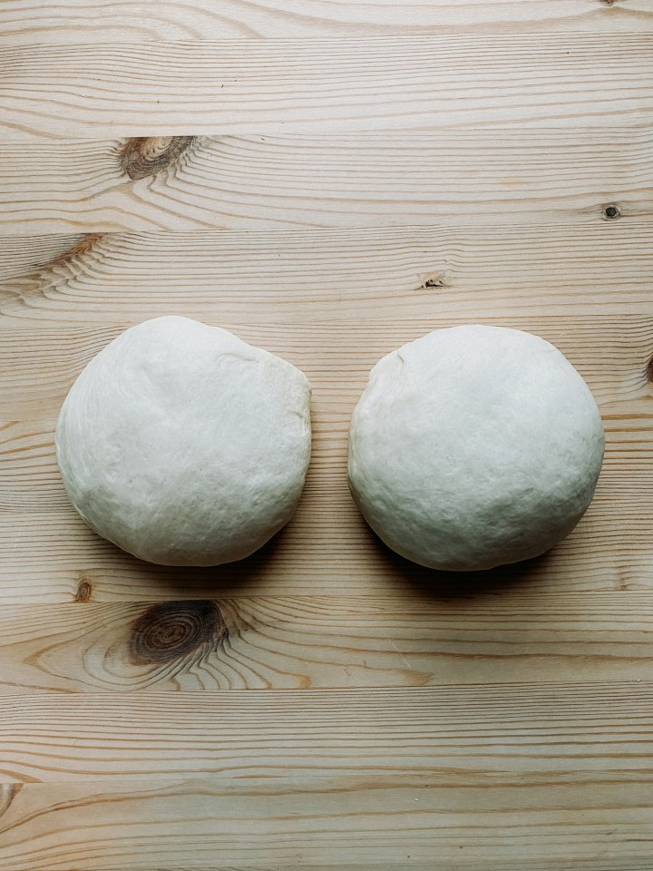 two balls of pizza dough resting on a wooden surface